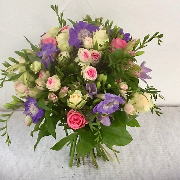 A bouquet of classic country flowers in shades of pink and cream including Avalanche and Sweetheart Roses, freesias, stocks, alstromeria and eucalyptus. Hand tied, aqua packed and presented in a gift bag.