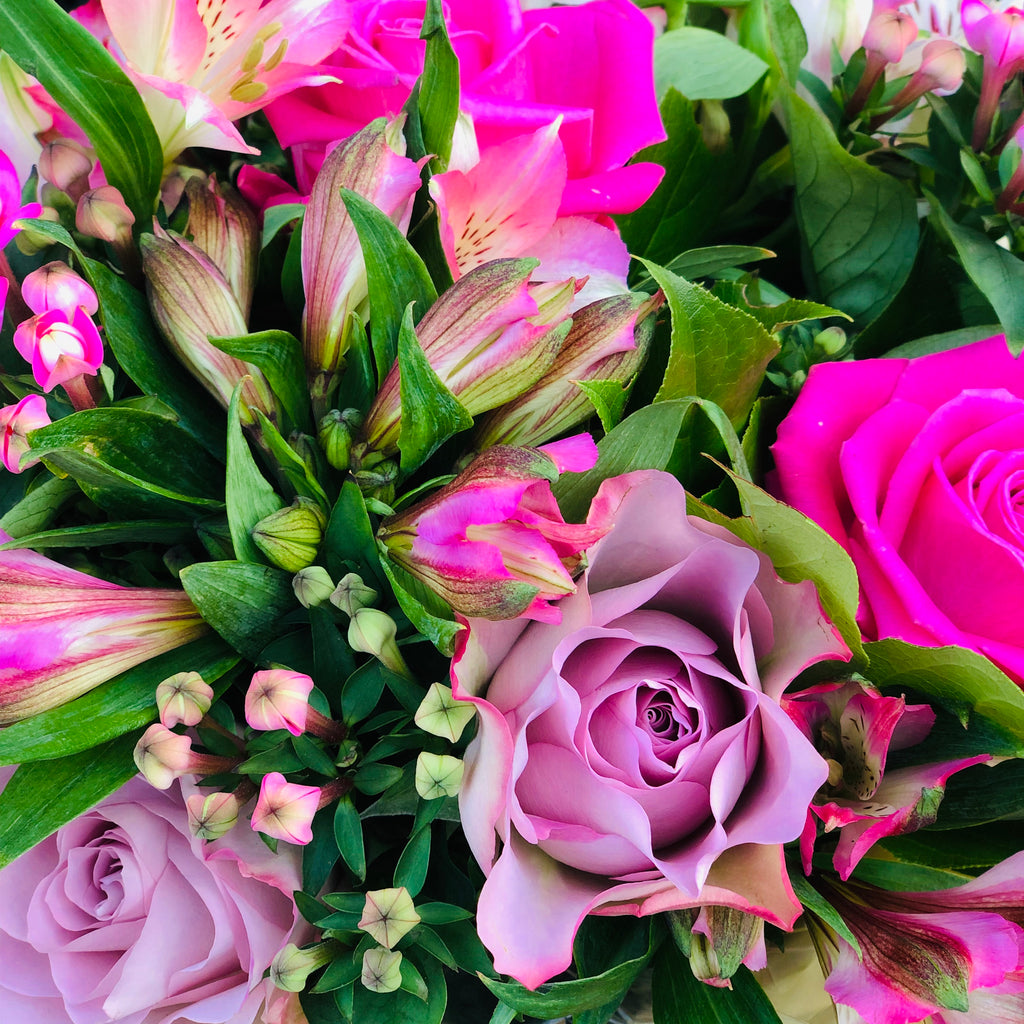 A hand-tied bouquet of dusky and rich pink roses, pink bouvardia and alstromeria flowers,  which is presented in an aqua-packed gift bag with tissue paper.