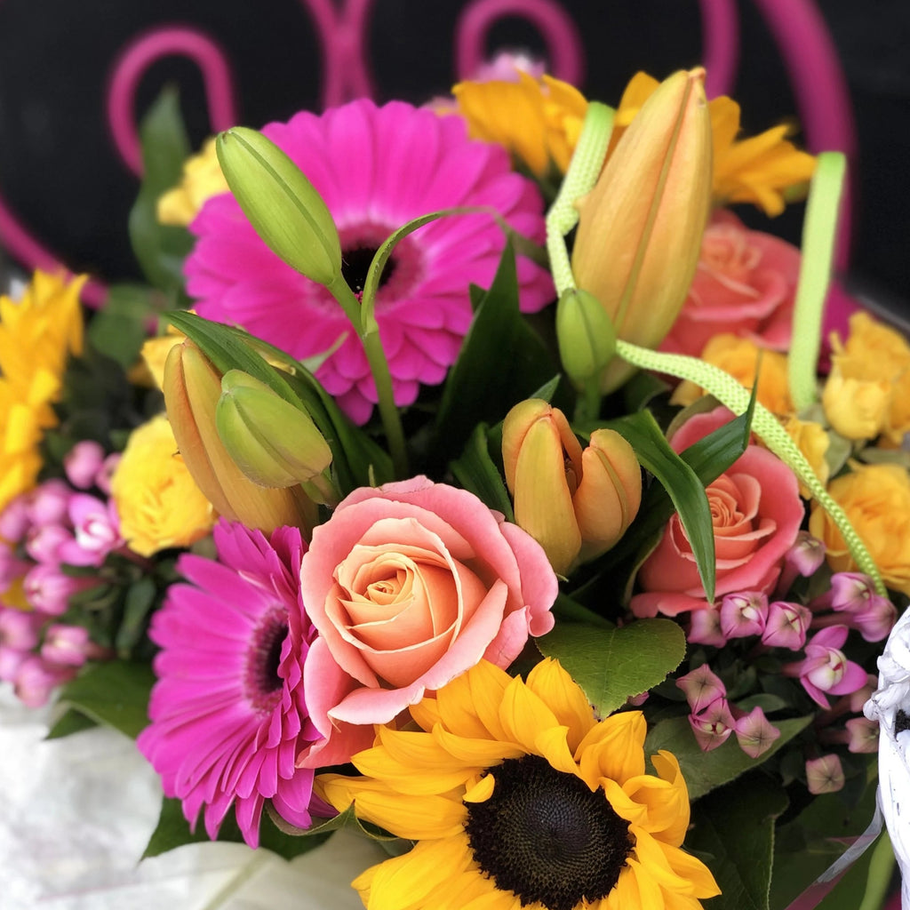 A beautifully colourful bouquet of fuschia pink gerberas, apricot lilies, sunflowers, peachy-pink roses and bouvardia, hand-tied, aqua-packed and presented in a gift bag with tissue paper.