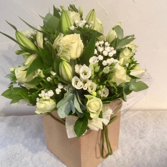 A beautiful bouquet of pure white flowers including white Lilies, Roses, Bouvardia, Freesias, Eustoma complemented with a selection of foliage. Hand tied, aqua packed and presented in a gift bag.