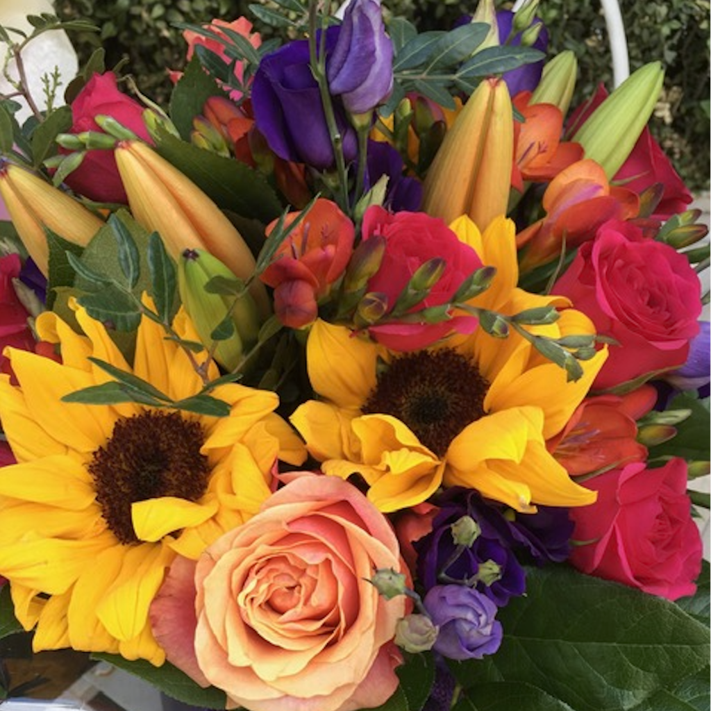 A stunning and bright bouquet including Sunflowers, Roses, Tulips, Lisianthus, Freesias and Lillies. Hand-tied in an aqua-pack and presented in a gift bag.