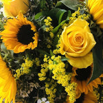 A bright bouquet of sunflowers, yellow roses, wax flower, and Solidago.  Aqua-packed and presented in a gift bag.