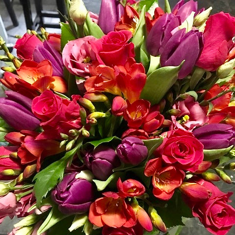 A stunning collection of Spring flowers with purple tulips, freesias, sweetheart roses, lisianthus and complementing foliage. Presented in an aqua-packed gift bag and tissue paper.
