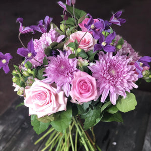 A bright bouquet with Chrysanthemums, Pink toned roses, trailing Clematis, and a foliage, hand tied, aqua packed and presented in a gift bag.