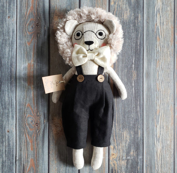"US stockist of Vasya & Vasya's handmade heirloom quality stuffed lion with embroidedred glasses on face.  Black suspender pants and light grey lion made from flax fabric, hypoallergenic filler, hand embroidered and handpainted face.  Measures approximately 15"" in height."
