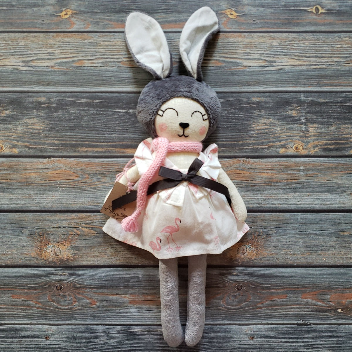 "US stockist of Vasya Vasya's heirloom quality girl bunny made from linen fabric, soft plush and hypoallergenic filler.  Cream color with grey head and ears.  Wears beautiful flamingo print dress with pink scarf.  Measures approximately 15""."