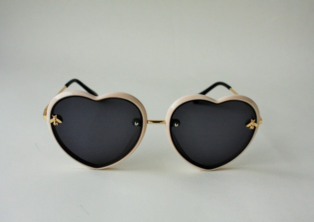 US stockist of Elle Porte's Queen Bee sunglasses.  Heart shaped frames with cream outline, complementary partial gold metal arms, nosepiece and two small gold bees.  Dark UV 400 lenses.