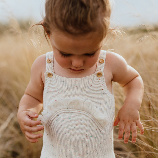US stockist of Grown Clothing's gender neutral rainbow romper.  Made from a chunky pearl knit in combed cotton.  Features a rainbow speckle throughout the yarn, adjustable wooden buttons on the straps and wooden buttons at crotch.  Self yarn fringe in the shape of a rainbow on chest.