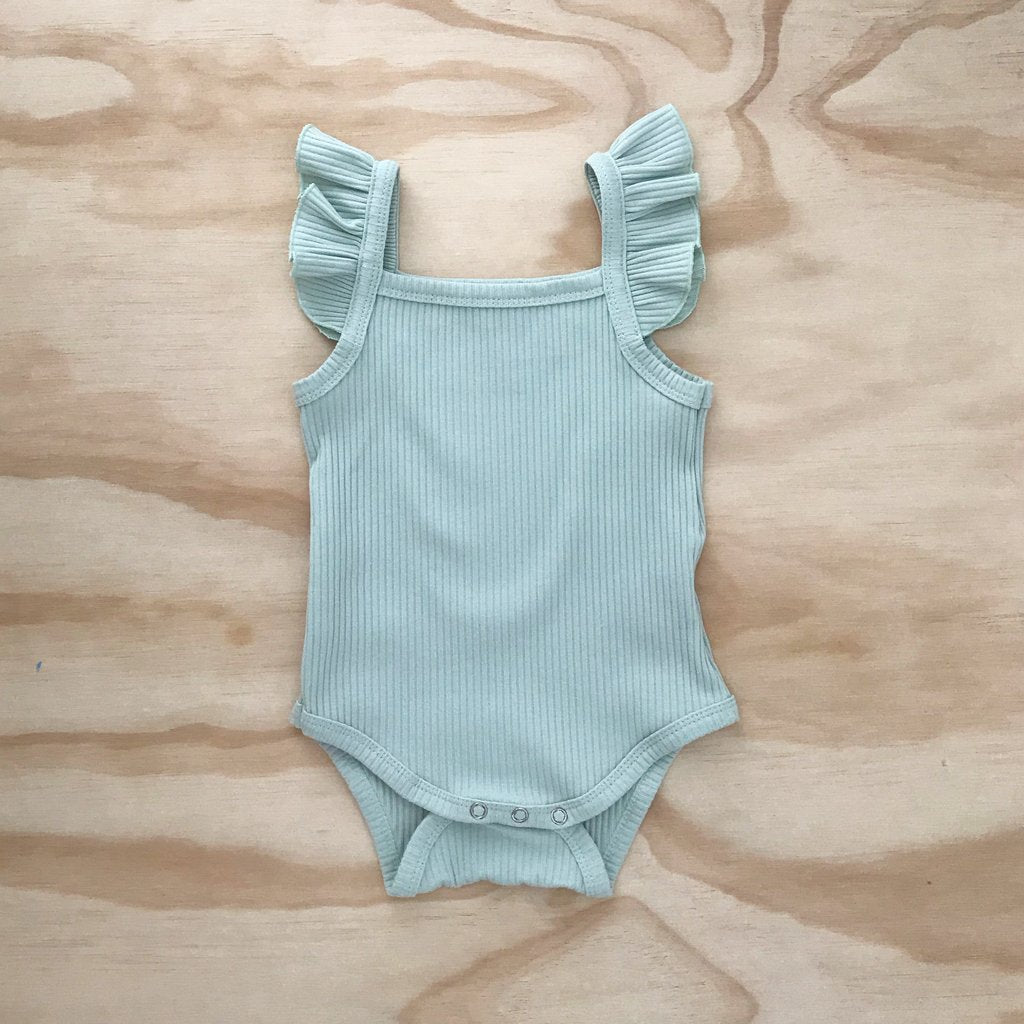 US stockist of Bel & Bow's ribbed cotton mint green bodysuit with flutter details on shoulder straps and snaps at crotch.