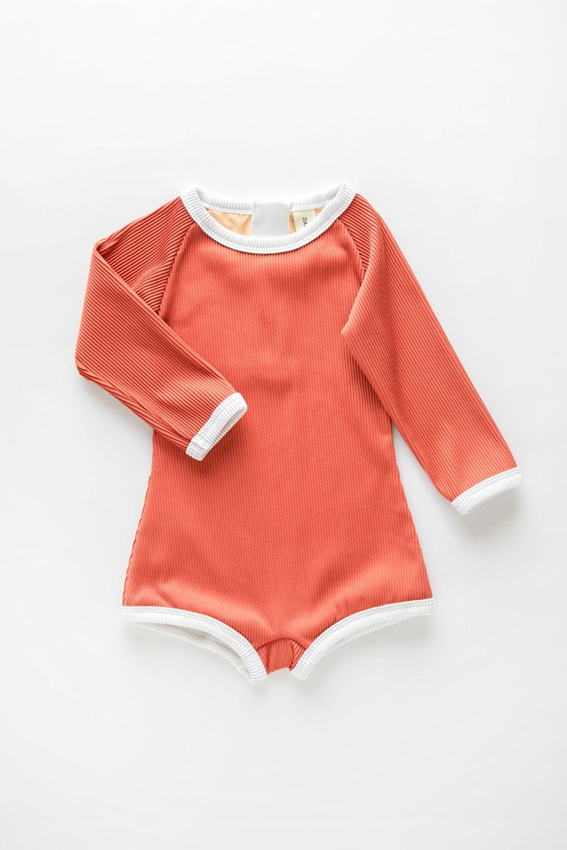 US stockist of Zulu & Zephyr's gender neutral, long sleeve mini rib rashie onesie in plum.  Sustainably made from econyl fabric, with a back Zip and fully lined.  UPF 50 fabric.