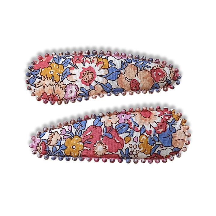 US stockist of Josie Joan's Amelia fabric hair clips.  Set of two fabric hair clips made from pale coloured fabric with multicolored flowers and  contrasting blue leaves.  Has scalloped edging.