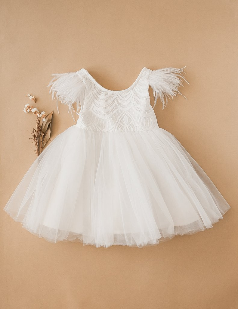 US stockist of Karibou Kids white Angelina Feather and Lace Dress.  Features 5 layer full skirt, lace bodice, scoop back and ostrich feather flutter sleeves.