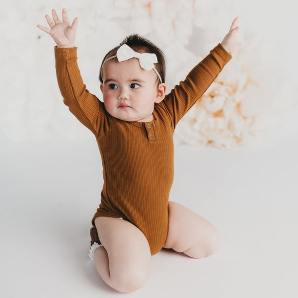 US stockist of Karibou Kids gender neutral, antique gold Willow long sleeve henley bodysuit in ribbed cotton blend.