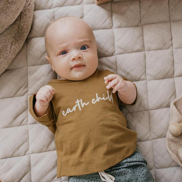 "US stockist of Buck & Baa's organic cotton ""Earth Child"" short sleeve t-shirt.  Boxy fit, with white ""Earth Child"" printed across the chest.  Ochre color."