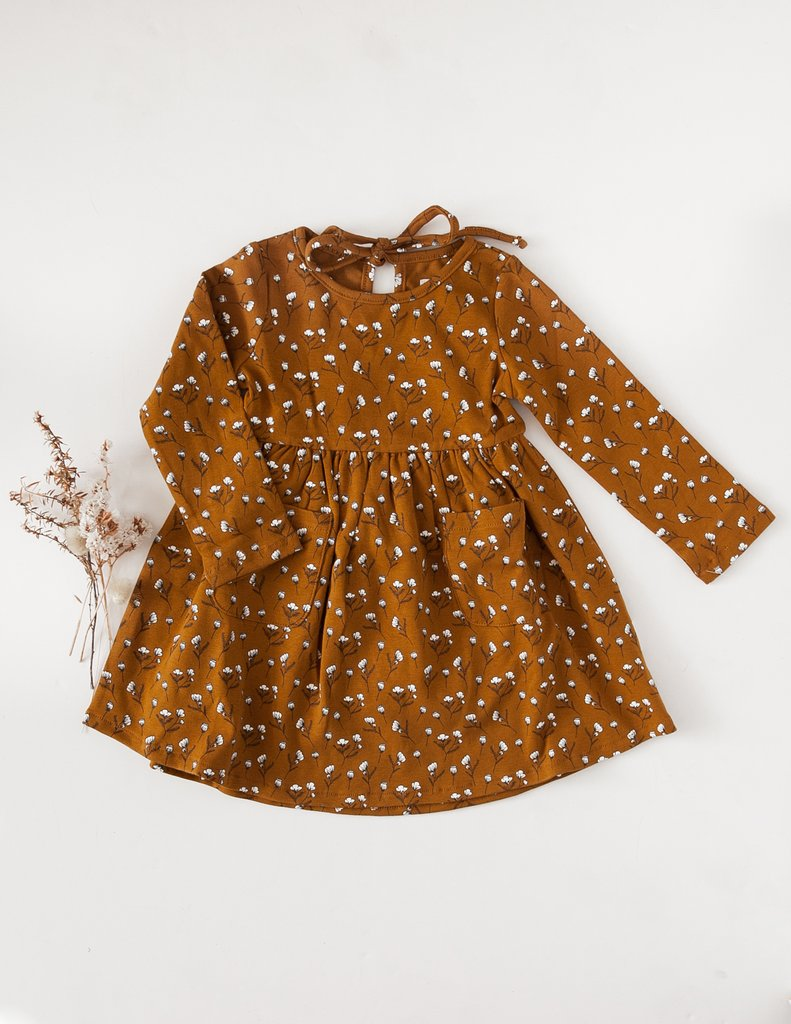 US stockist of Karibou Kid's Long Sleeve Cotton Puff pocket dress in golden acorn. Featues two front pockets and ties at back of neck.