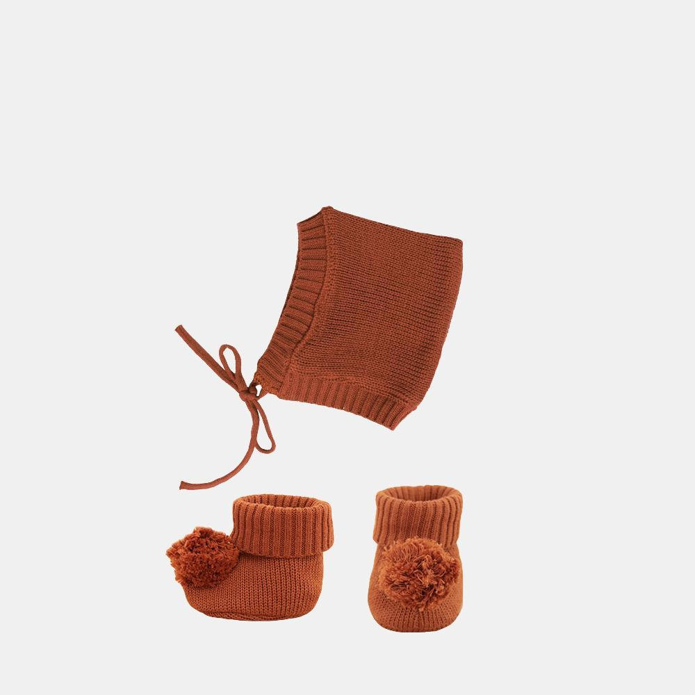 US stockist of Olli Ella's Dinkum Doll Knit Umber Set.  Features cotton knit bonnet and hard sole knit booties with pom poms on front.
