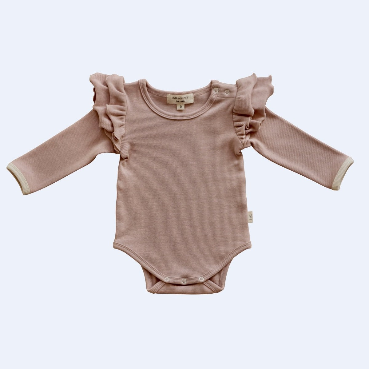 US stockist of India + Grace The Label's dusty pink long sleeved ribbed cotton bodysuit.  Features crotch snaps and beautiful ruffles at shoulder.