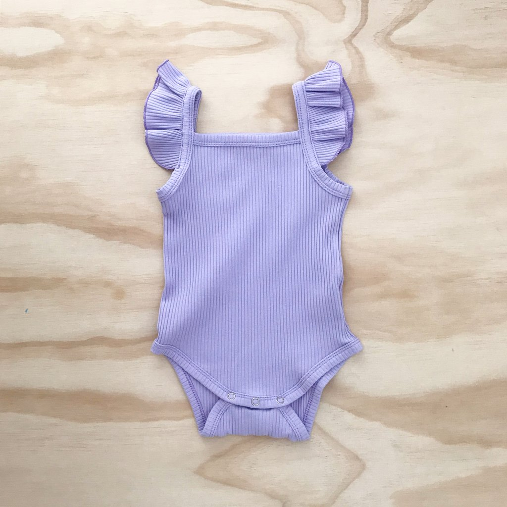 US stockist of Bel & Bow's ribbed cotton lilac bodysuit with flutter details on shoulder straps and snaps at crotch.