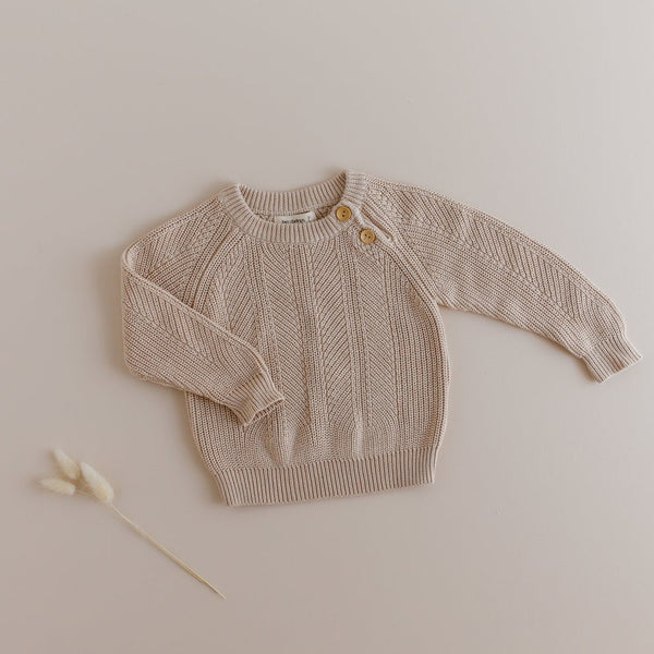 US stockist of Two Darlings gender neutral stone knit sweater.  Made from 100% cotton with two wood like buttons on the left shoulder.  Soft and stretchy.