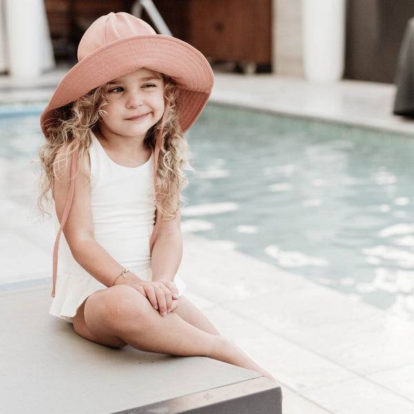 US stockist of Fini the Label's gender neutral, floppy swim hat in cocoa. Features elongated back for added sun protection, chin strap and adjustable bow around crown for better fit. Brim is medium stiffness and can be flipped up at front.  Made from nylon/spandex and is quick drying.
