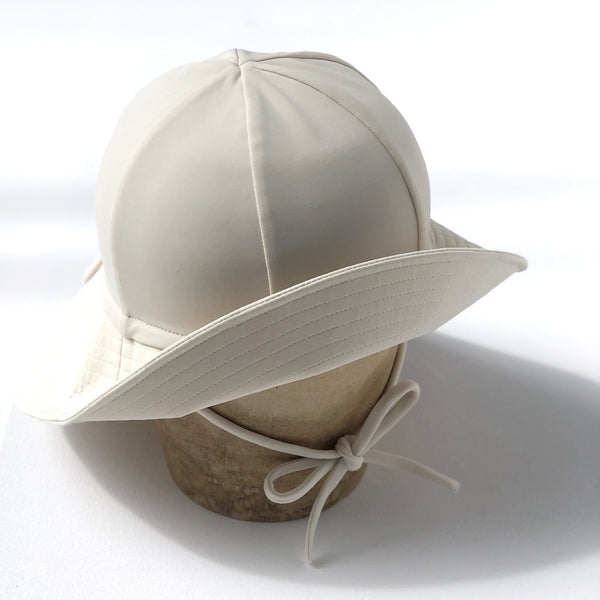 US stockist of Fini the Label's gender neutral, floppy swim hat in cream. Features elongated back for added sun protection, chin strap and adjustable bow around crown for better fit. Brim is medium stiffness and can be flipped up at front.  Made from nylon/spandex and is quick drying.