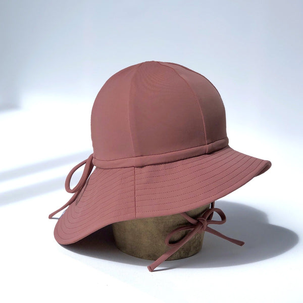 US stockist of Fini the Label's gender neutral, floppy swim hat in marsala. Features elongated back for added sun protection, chin strap and adjustable bow around crown for better fit. Brim is medium stiffness and can be flipped up at front.  Made from nylon/spandex and is quick drying.
