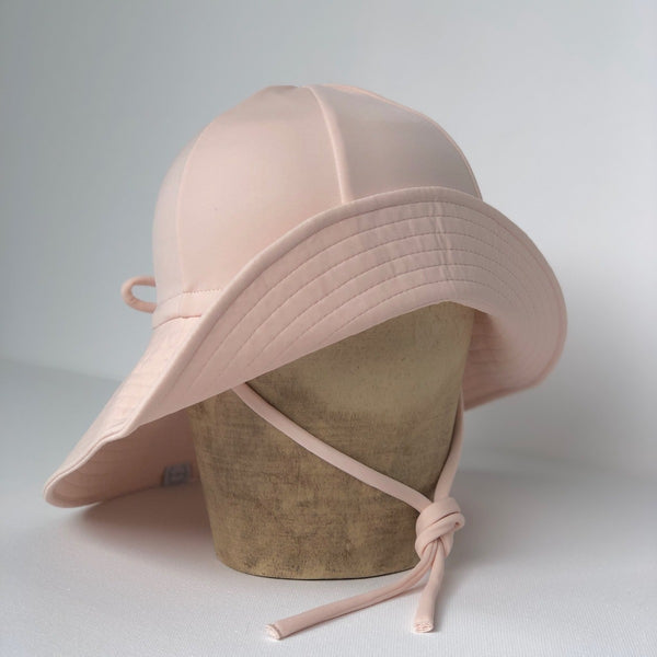 US stockist of Fini the Label's floppy swim hat in pale pink. Features elongated back for added sun protection, chin strap and adjustable bow around crown for better fit. Brim is medium stiffness and can be flipped up at front.  Made from nylon/spandex and is quick drying.