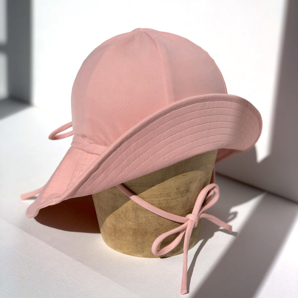 US stockist of Fini the Label's floppy swim hat in pink. Features elongated back for added sun protection, chin strap and adjustable bow around crown for better fit. Brim is medium stiffness and can be flipped up at front.  Made from nylon/spandex and is quick drying.