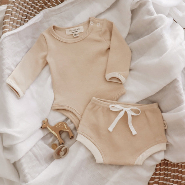 US stockist of India + Grace The Label's gender neutral, beige long sleeved ribbed cotton bodysuit.  Features crotch snap.