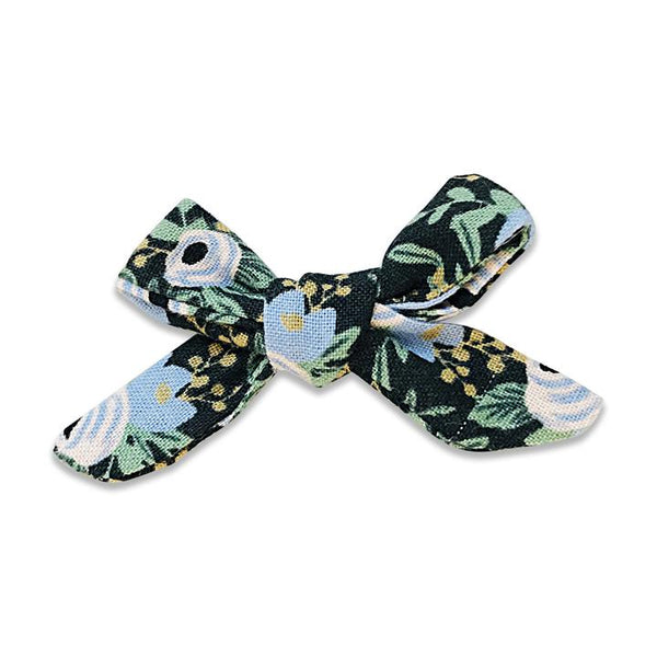 US stockist of Josie Joan's Jemima petite bow hair clip.  Dark colored fabric with blue and white flowers with contrasting green foilage and yellow berries.