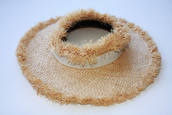 A  full, gender neutral circular visor with raw straw edge around the brim and the crown.  Cream satin ribbon detail.