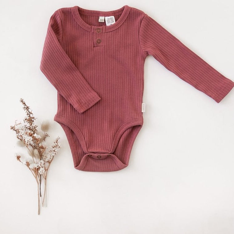 US stockist of Karibou Kids garden rose pink Willow long sleeve henley bodysuit in ribbed cotton blend.