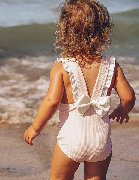 US stockist of Karibou Kids Strawberry Sundae onepiece swimsuit.  Pale pink ribbed fabric with white ruffles on straps and gorgeous white statement bow at the back.