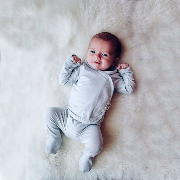 Stockist of Bonsie's rayon blend mist light grey footie.  Top section has velcro wrap body which can be undone for skin to skin contact.  Elastic waist that can be pulled down for easy diaper changes.
