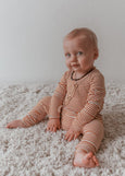 US stockist of Two Darlings gender neutral Mustard Stripe stretch rib cotton bodysuit. Long Sleeves with 4 non functional wooden buttons kimono style across the front.