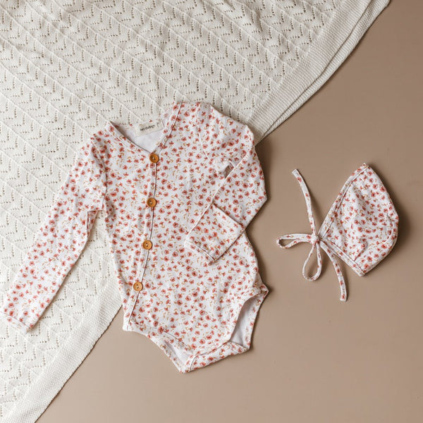 US stockist of Two Darlings gender neutral Posey Floral stretch cotton bodysuit. Long Sleeves with 4 non functional wooden buttons kimono style across the front.