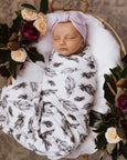 US stockist of Snuggle Hunny Kid's white cotton jersey wrap with brown quill feather print. Comes with matching beanie.