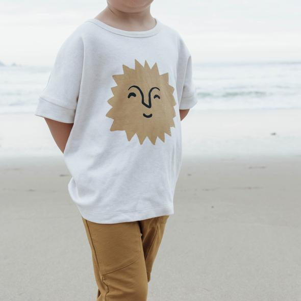 US stockist of Buck & Baa's short sleeve organic cotton Ra Sun t-shirt.  Made from white organic cotton with yellow smiling sun printed on the front.  Gender neutral.