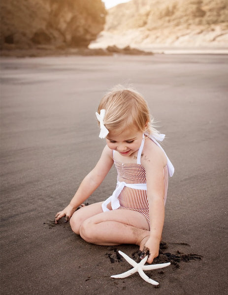 US stockist of Karibou Kids Girls Vintage Style Halter Neck Swimsuit - rust striped with sweetheart neckline, white tie belt around waist and white halter neck tie.
