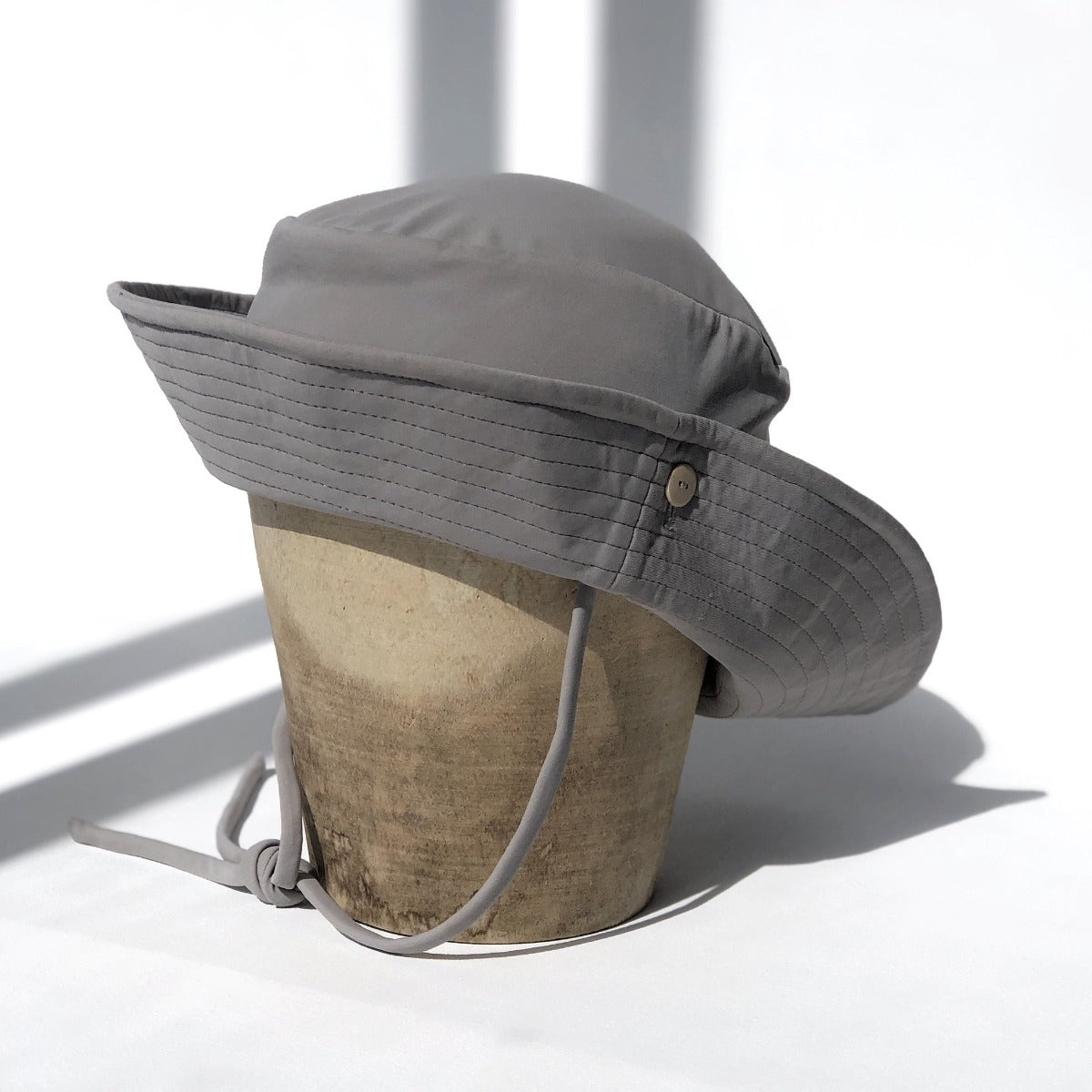 US stockist of Fini the Label's gender neutral, sailor swim hat in mushroom. Features elongated back for added sun protection, wide brim and chin strap. Brim is medium stiffness and can be flipped up at front. Sides can be worn buttoned up for that sailor look.  Made from nylon/spandex and is quick drying.