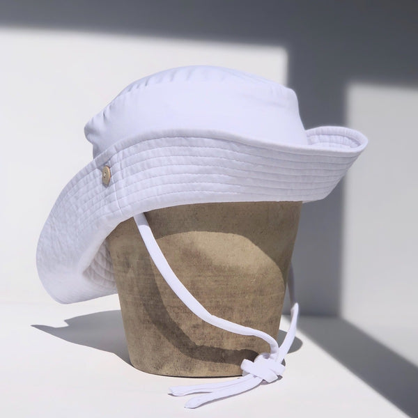 US stockist of Fini the Label's gender neutral, sailor swim hat in white. Features elongated back for added sun protection, wide brim and chin strap. Brim is medium stiffness and can be flipped up at front. Sides can be worn buttoned up for that sailor look.  Made from nylon/spandex and is quick drying.