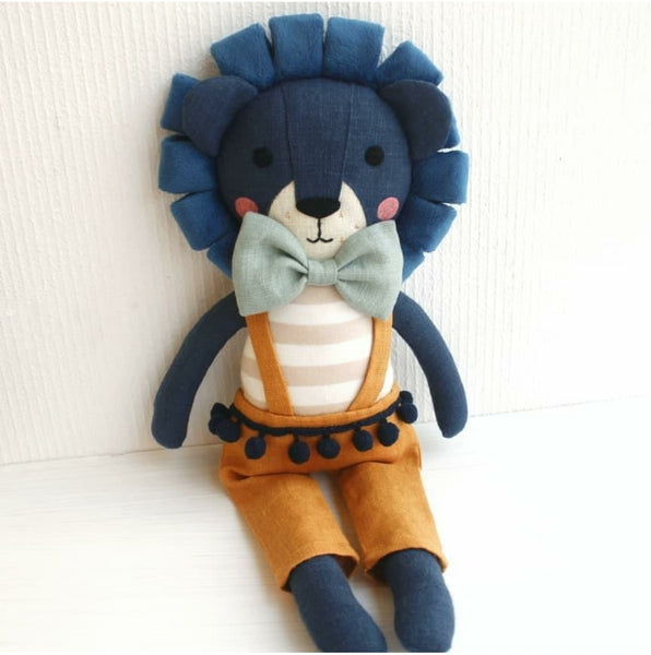 "US stockist of Vasya & Vasya's handmade heirloom quality stuffed royal blue lion.  Mustard suspender pants with blue pom pom belt, light blue bow tie and royal blue lion made from flax/cotton knit  fabric, hypoallergenic filler, hand embroidered and handpainted face.  Measures approximately 15"" in height."