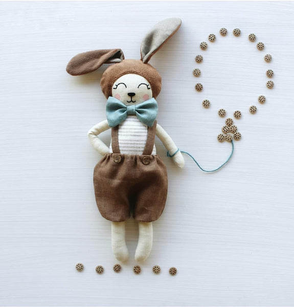"US stockist of Vasya Vasya's heirloom quality, handmade chocolate bunny.  Made from linen fabric, hypoallergenic fillers and soft plush, this little bunny measures approximately 15"".  He wears chocolate suspender shorts with wooden buttons and has a light blue bow tie."