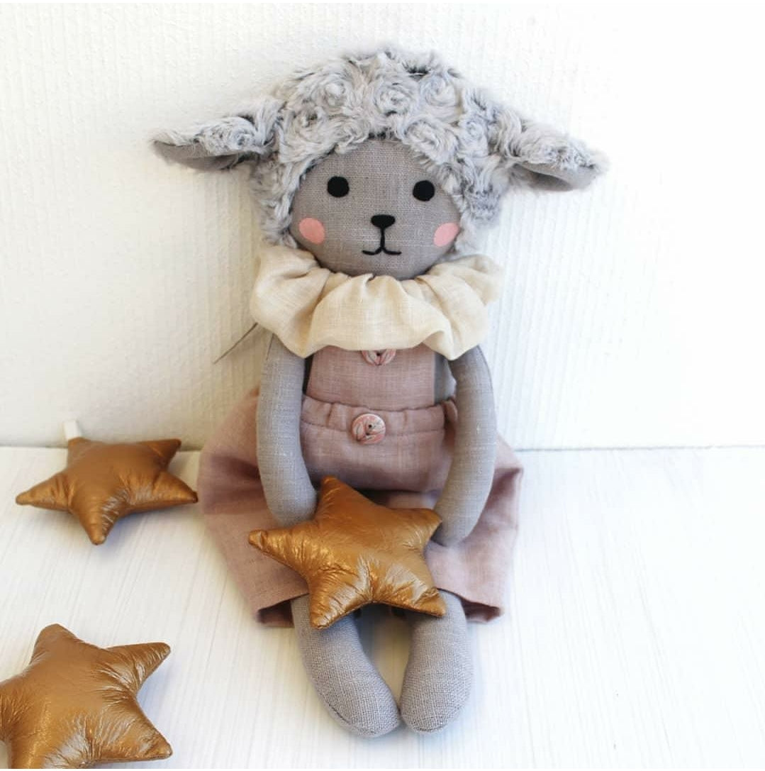 "US stockist of Vasya Vasya's heirloom quality, hand made grey linen lamb.  She has soft grey plush ears and curls on her head.  Wears a light linen pink jumpsuit and cream linen ruff around her neck.  Measures 15"" in height."