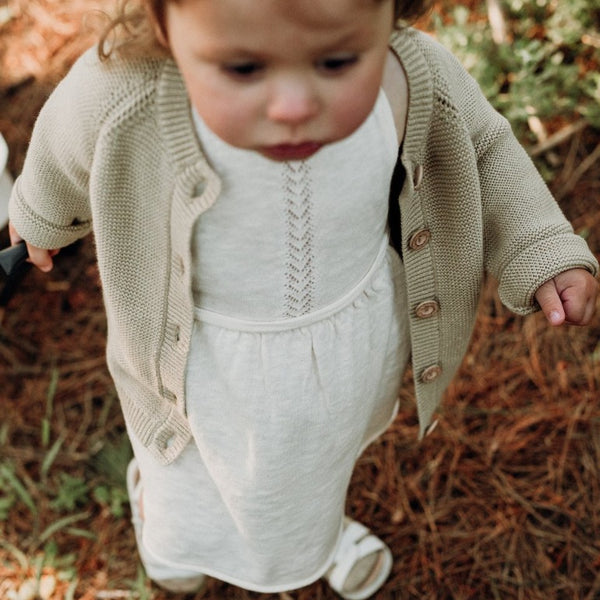 US stockist of Grown Clothing's slub linen dress in oat.  Made from a cotton line blend, with adjustable straps that tie in a bow at the back.  Features a rolled hem and sweet pointelle knit details down the front of the dress.