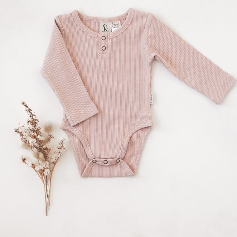 US stockist of Karibou Kids soft pink Willow long sleeve henley bodysuit in ribbed cotton blend.