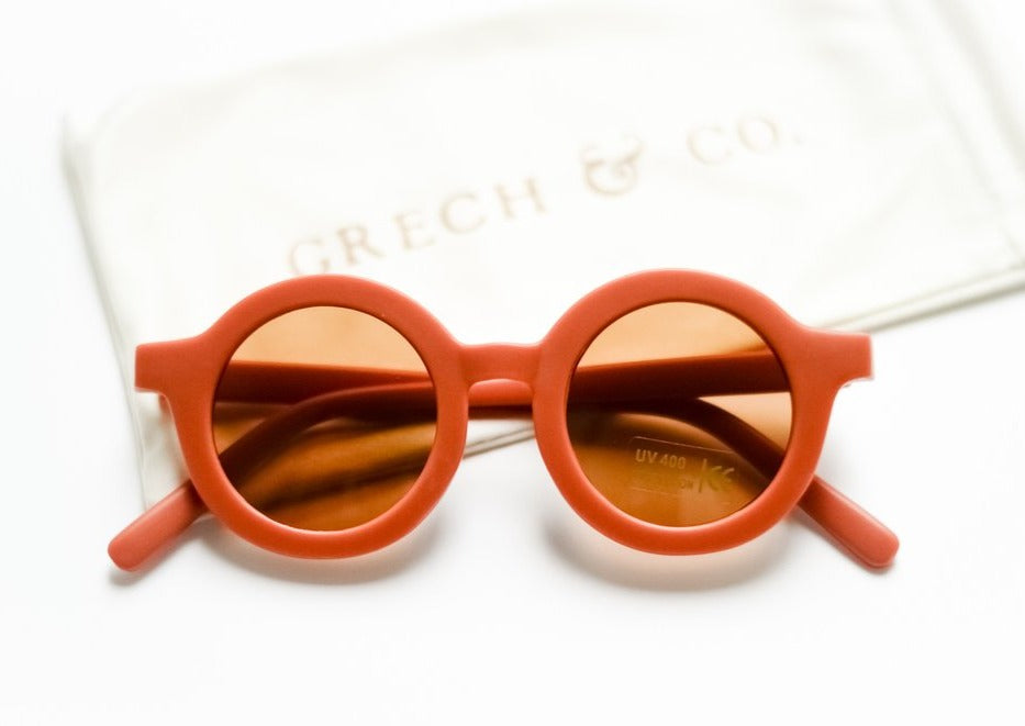 US stockist of Grech & Co's gender neutral sustainable sunglasses.  Made from recycled plastic, with round amber lens with UV 400 protection in a rust color.