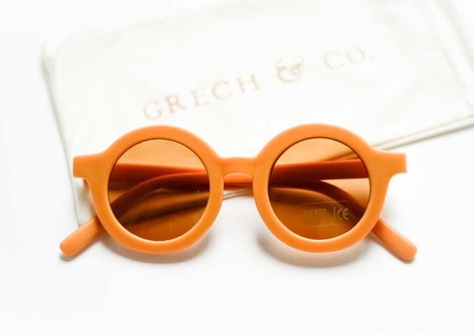 US stockist of Grech & Co's gender neutral sustainable sunglasses.  Made from recycled plastic, with round amber lens with UV 400 protection in a golden color.