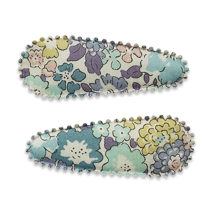 US stockist of Josie Joan's Suzanne set of two fabric hair clips.  Pale colored fabric with pastel flowers in hues of pink, purple, blue and yellow. Features scalloped edges.