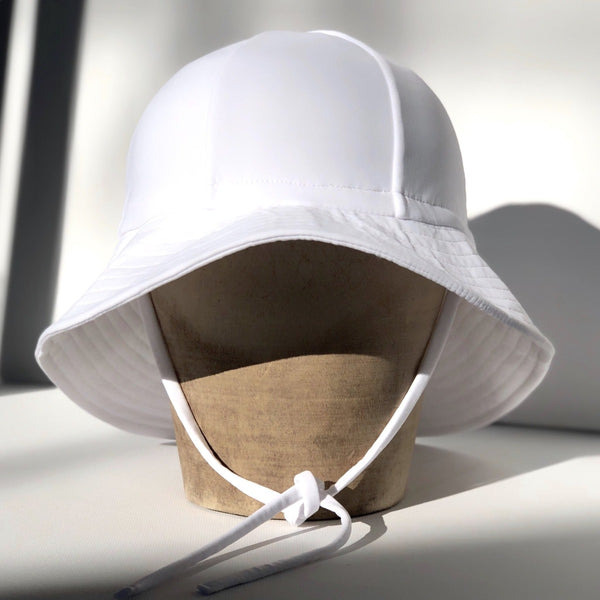 US stockist of Fini the Label's gender neutral floppy swim hat in white. Features elongated back for added sun protection, chin strap and adjustable bow around crown for better fit. Brim is medium stiffness and can be flipped up at front.  Made from nylon/spandex and is quick drying.